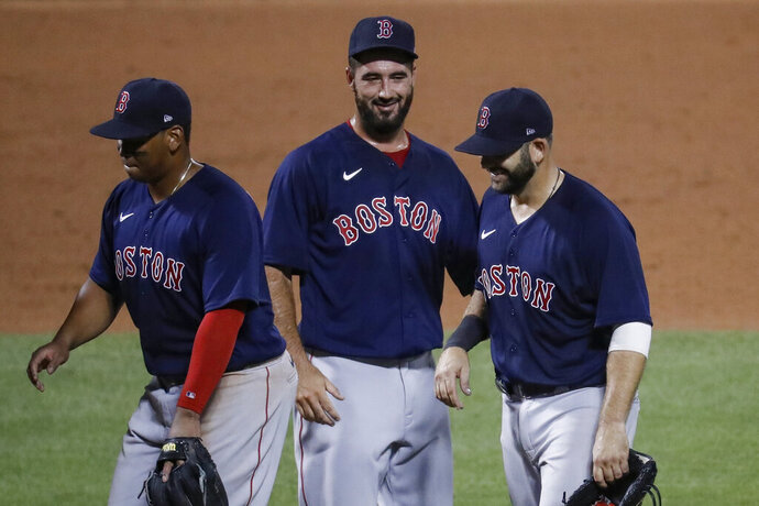 Boston Red Sox first baseman Mitch Moreland, right, celebrates with relief pitcher Brandon Workman, center, after the Red Sox defeated the New York Mets 6-5 in a baseball game Wednesday, July 29, 2020, in New York. (AP Photo/John Minchillo)