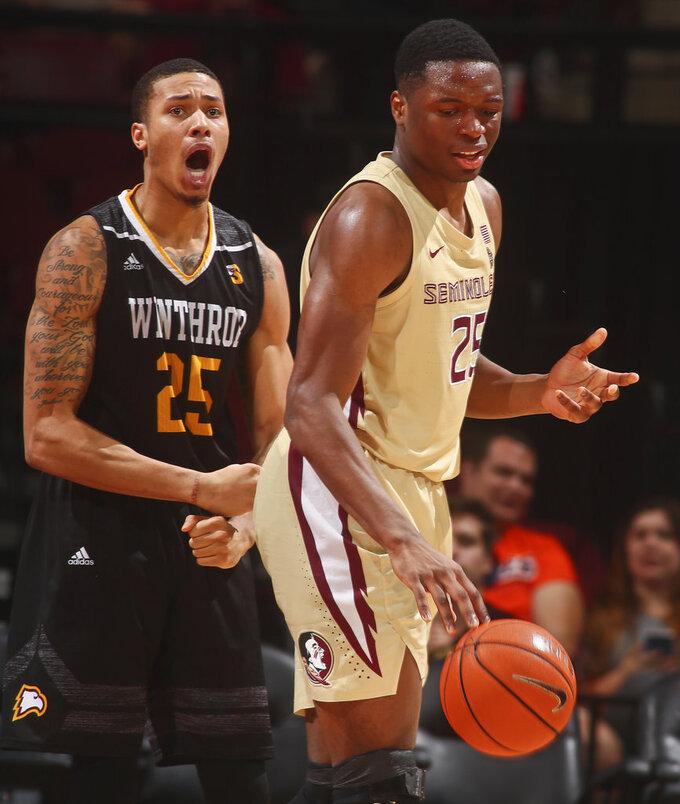 Winthrop forward Josh Ferguson (25) reacts after making a basket and getting fouled as Florida State forward Mfiondu Kabengele (25) controls the ball in the second half of an NCAA college basketball game in Tallahassee, Fla., Tuesday, Jan. 1, 2019. Florida State won 87-76. (AP Photo/Phil Sears)