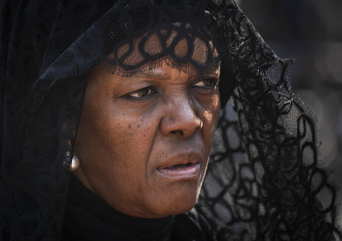 FILE- In this Thursday, Sept. 12, 2019, file photo, widow Grace Mugabe wears a black veil as she follows the casket of former president Robert Mugabe to an air force helicopter for transport to a stadium where it will lie in state, at his official residence in the capital Harare, Zimbabwe. Known as a strong-willed woman with political ambitions, Grace Mugabe rose from being one of the president's secretaries to become first lady. (AP Photo/Ben Curtis, File)