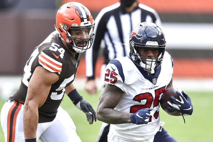Houston Texans running back Duke Johnson (25) rushes as Cleveland Browns defensive end Olivier Vernon (54) pursues during the first half of an NFL football game, Sunday, Nov. 15, 2020, in Cleveland. (AP Photo/David Richard)