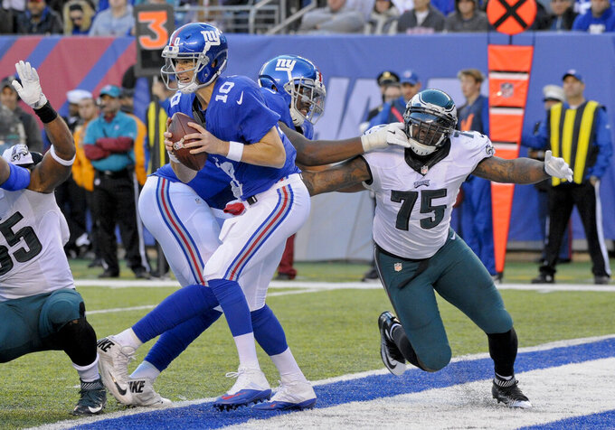 FILE - In this Sunday, Nov. 6, 2016 file photo, New York Giants quarterback Eli Manning (10) moves out of the pocket under pressure from Philadelphia Eagles defensive end Vinny Curry (75) during the fourth quarter of an NFL football game in East Rutherford, N.J. The New York Jets added experience and depth on both sides of the ball with their latest moves in free agency. The team announced Wednesday, March 24, 2021 it signed former Philadelphia Eagles defensive end Vinny Curry, who'll provide an already formidable D-line a veteran pass-rushing presence. The Jets also agreed to terms on a one-year contract with running back Tevin Coleman.  (AP Photo/Bill Kostroun, File)