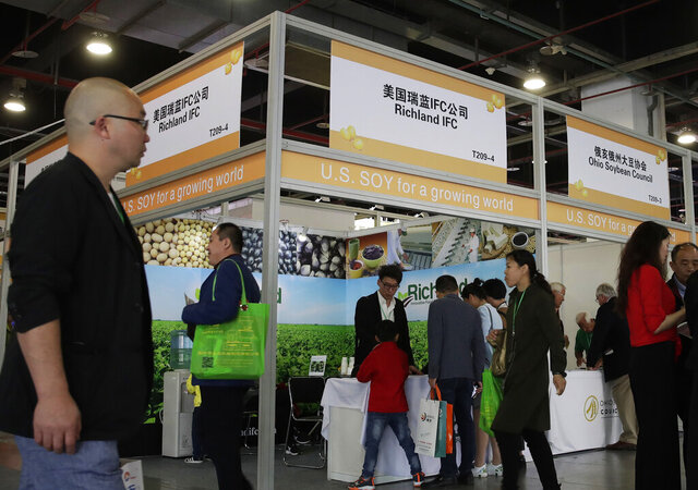 FILE - In this April 12, 2018, file photo, visitors walk by U.S. soybean companies' booths at the international soybean exhibition in Shanghai, China. President Donald Trump likes to joke that America's farmers have a nice problem on their hands: They're going to need bigger tractors to keep up with surging Chinese demand for their soybeans and other agricultural goods under a preliminary deal between the world's two largest economies. Yet skeptics are questioning how much China has committed to buy. (AP Photo/Andy Wong, File)