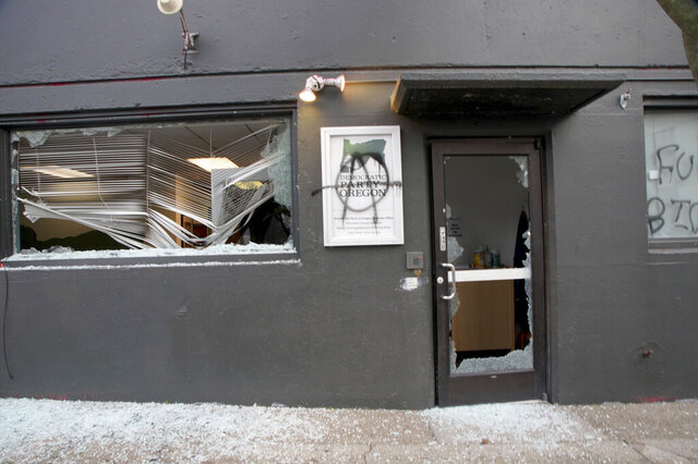 A group of protesters carrying anti-President Joe Biden and anti-police signs marched in the streets and damaged the headquarters of the Democratic Party of Oregon, Wednesday, Jan. 20, 2021, in Portland, Ore. (Beth Nakamura/The Oregonian via AP)