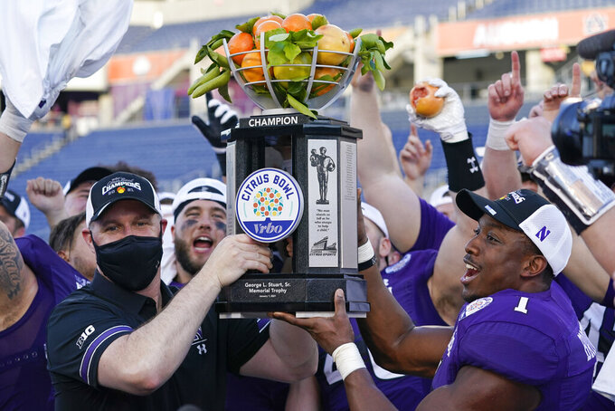 Northwestern head coach Pat Fitzgerald, front left, and Northwestern running back Jesse Brown (1) hold up the Citrus Bowl trophy after defeating Auburn in an NCAA college football game, Friday, Jan. 1, 2021, in Orlando, Fla. (AP Photo/John Raoux)