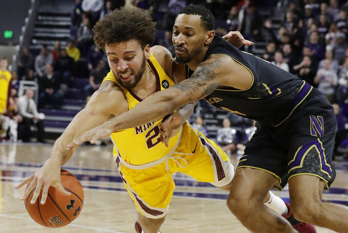 Minnesota guard Gabe Kalscheur, left, and Northwestern guard Ryan Taylor reach for the ball during the first half of an NCAA college basketball game Thursday, Feb. 28, 2019, in Evanston, Ill. (AP Photo/Nam Y. Huh)