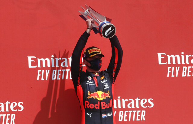 Red Bull driver Max Verstappen of the Netherlands holds up the trophy on the podium after taking first place in the 70th Anniversary Formula One Grand Prix at the Silverstone circuit, Silverstone, England, Sunday, Aug. 9, 2020. (AP Photo/Frank Augstein,Pool)