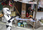 Members of a youth group in Star Wars costumes entertain locals along a road in Malabon, Metro Manila, Philippines, Thursday, April 30, 2020. The youth group walks along streets to give residents some form of entertainment as they endure the continued community quarantine and to remind them to stay at home to prevent the spread of the new coronavirus. (AP Photo/Aaron Favila)