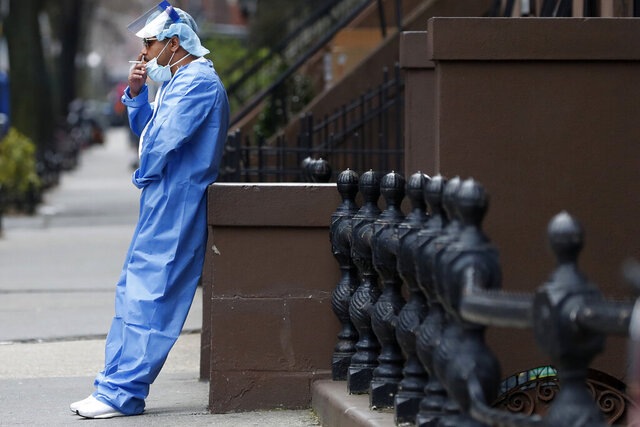 Wearing his personal protective equipment, emergency room nurse Brian Stephen leans against a stoop as he takes a break from his work at the Brooklyn Hospital Center, Sunday, April 5, 2020, in New York. Located in downtown Brooklyn, the hospital is one of several in the New York area that has been treating high numbers of coronavirus patients during the pandemic. (AP Photo/Kathy Willens)