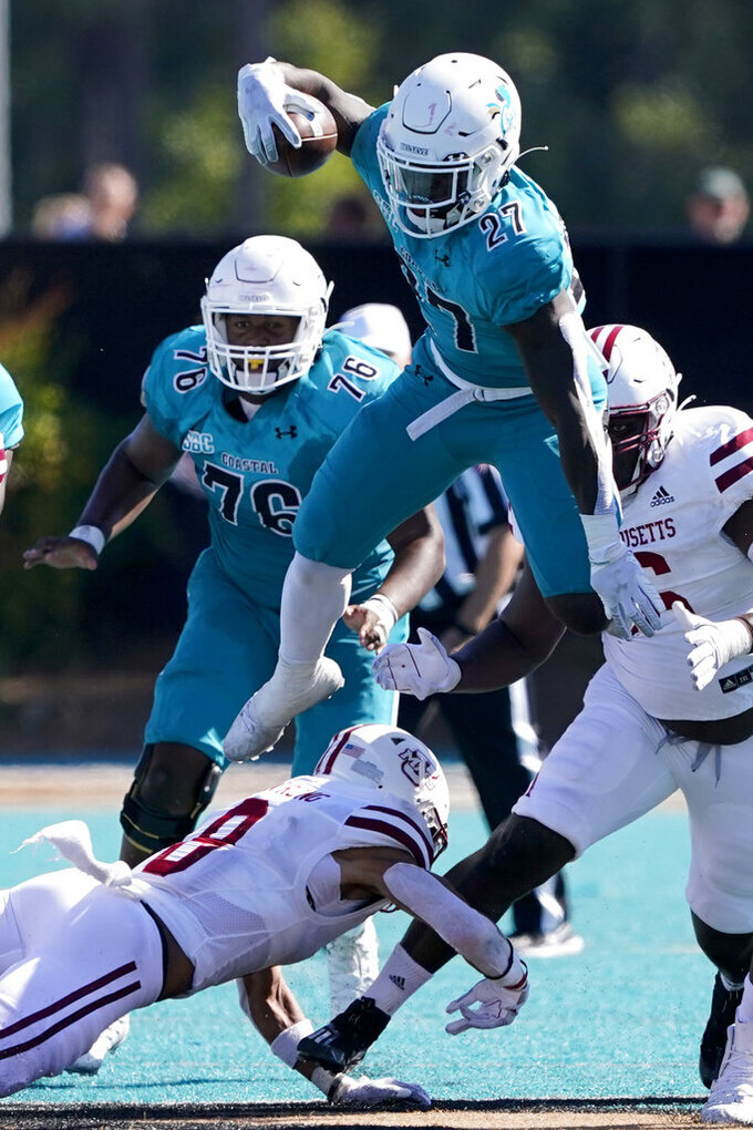 Coastal Carolina running back CJ Beasley leaps over Massachusetts defensive back Tristan Armstrong during the second half of an NCAA college football game on Saturday, Sept. 25, 2021, in Conway, S.C. (AP Photo/Chris Carlson)