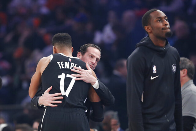 Brooklyn Nets head coach Kenny Atkinson embraces Brooklyn Nets guard Garrett Temple (17) following a moment of silence for retired Los Angeles Lakers star Kobe Bryant who died in a helicopter crash earlier in the day, before the start of an NBA basketball game in New York, Sunday, Jan. 26, 2020. (AP Photo/Kathy Willens)
