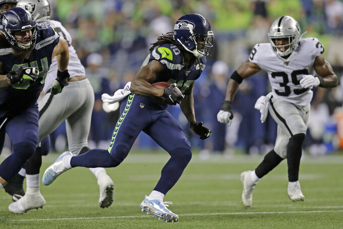 Seattle Seahawks running back Bo Scarbrough rushes against Oakland Raiders free safety Jordan Richards, right, during the second half of an NFL football preseason game Thursday, Aug. 29, 2019, in Seattle. (AP Photo/Stephen Brashear)