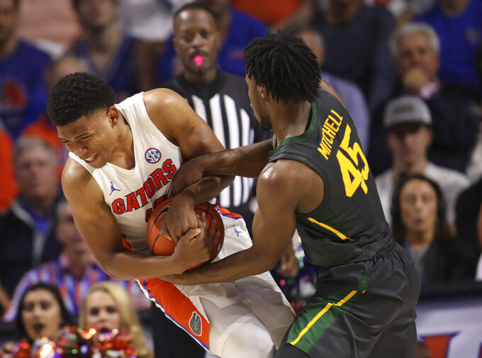 Baylor guard Davion Mitchell (45) forces a jump ball with Florida guard Noah Locke (10) during the second half of an NCAA college basketball game Saturday, Jan. 25, 2020, in Gainesville, Fla. (AP Photo/Matt Stamey)