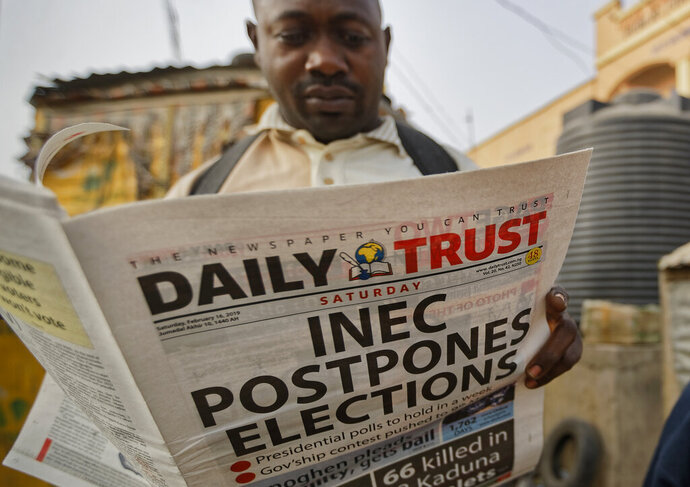 A man reads a copy of a newspaper which managed to print the news of the postponement in time, in the morning at a newspaper stand in Kano, northern Nigeria Saturday, Feb. 16, 2019. Nigeria's electoral commission delayed the presidential election until Feb. 23, making the announcement a mere five hours before polls were set to open Saturday. (AP Photo/Ben Curtis)