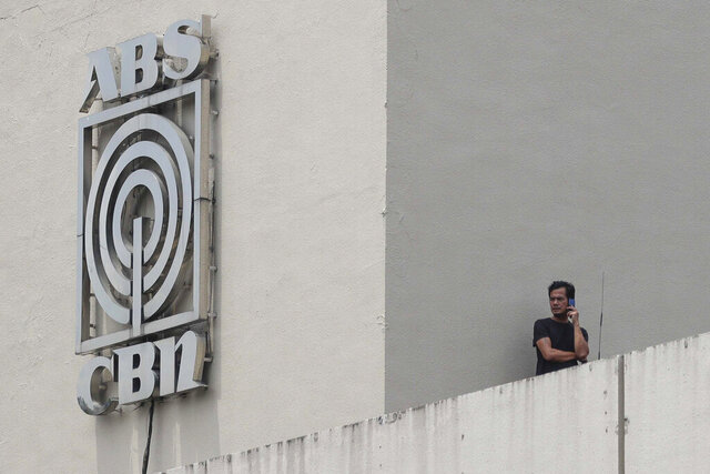 A man stands next to a logo at the headquarters of broadcast network ABS-CBN Corp. on Wednesday May 6, 2020 in Manila, Philippines. Philippine church and business leaders expressed alarm Wednesday over a government agency's shutdown of the country's largest TV and radio network, which has been a major provider of news on the coronavirus pandemic. (AP Photo/Aaron Favila)
