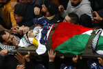 Palestinians carry the body of policeman Tariq Badwan during his funeral in the West Bank village of Azoun near Qalqilya, Friday, Feb. 7, 2020. Badwan was shot while standing at the entrance of a police station in Jenin, where Israeli forces clashed with Palestinians while demolishing the home of an alleged militant. He did not appear to have been involved in the clashes. (AP Photo/Majdi Mohammed)