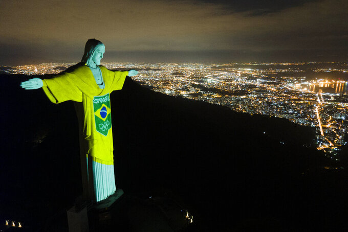 The colors of the Brazilian Olympic team are projected on the statue of Christ the Redeemer by the Brazilian Olympic Committee as a reminder of how sport can inspire in the fight against COVID-19, one hundred days before the Tokyo Olympic Games, in Rio de Janeiro, Brazil, Wednesday, April 14, 2021. (AP Photo/Lucas Dumphreys)