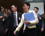 FILE - In this Oct. 17, 2019, file photo, Hong Kong Chief Executive Carrie Lam, center, arrives at chamber of the Legislative Council in Hong Kong. Hong Kong is feuding with Taiwan over a fugitive murder suspect whose case indirectly sparked the protests in Hong Kong over an extradition bill. Hong Kong officials pleaded on Tuesday, Oct. 22, for authorities in Taiwan to let the man surrender himself for killing his girlfriend while visiting the self-ruled island last year.(AP Photo/Vincent Yu, File)