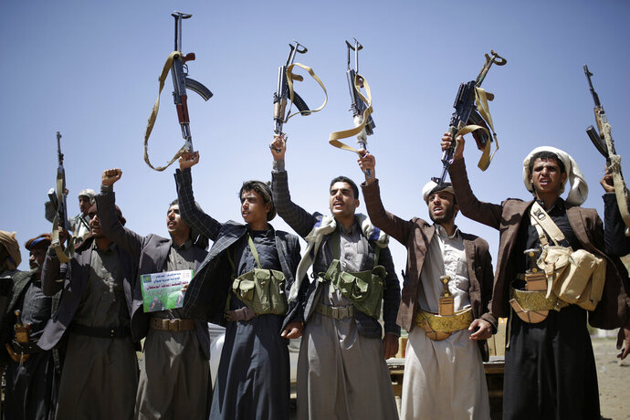 FILE - In this Sept. 21, 2019 file photo, Shiite Houthi tribesmen hold their weapons as they chant slogans during a tribal gathering showing support for the Houthi movement, in Sanaa, Yemen. Saudi Arabia and Yemen's Iran-backed Houthi  rebels are holding indirect, behind-the-scenes talks to end the impoverished Arab country's devastating five-year war. Officials from both sides have told The Associated Press, Wednesday, Nov. 13, 2019, that the negotiations are taking place with Oman, which borders both Yemen and Saudi Arabia, as mediator. (AP Photo/Hani Mohammed, File)