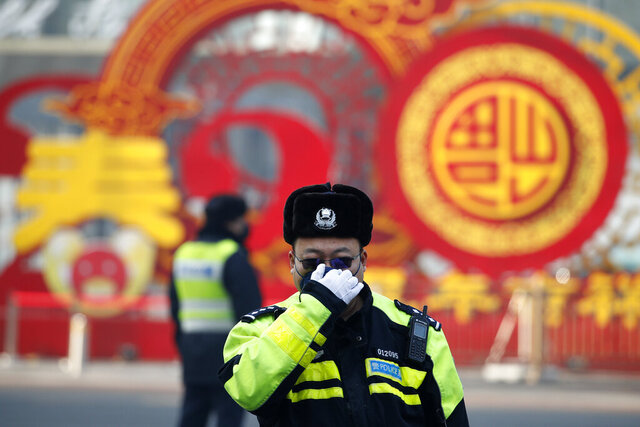 A traffic policeman adjusts his mask on a street in Beijing, Sunday, Feb. 9, 2020. China's coronavirus death toll on Sunday have surpassed the number of fatalities in the 2002-2003 SARS epidemic, but fewer new cases were reported in a possible sign its spread may be slowing as other nations step up efforts to block the disease. (AP Photo/Andy Wong)