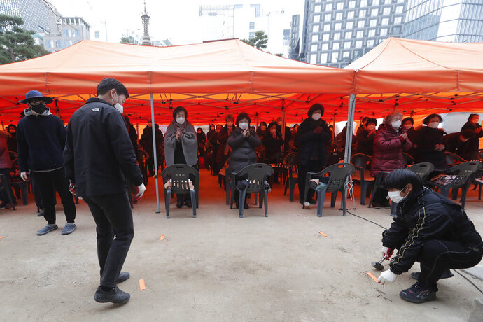 Workers mark social distancing signs as parents wearing face masks pray during a service to wish for their children's success on the eve of the college entrance exam at the Jogyesa Buddhist temple in Seoul, South Korea, Wednesday, Dec. 2, 2020. About 490,000 high school seniors and graduates across the country are expected to take the College Scholastic Ability Test. (AP Photo/Ahn Young-joon)