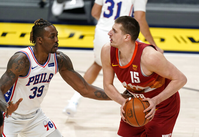 Philadelphia 76ers center Dwight Howard, left, defends as Denver Nuggets center Nikola Jokic looks to take a shot in the first half of an NBA basketball game Tuesday, March 30, 2021, in Denver. (AP Photo/David Zalubowski)