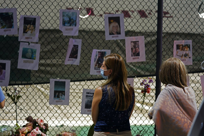 Angelica Pulido looks at a makeshift memorial with photos of some of the missing people near the site of an oceanfront condo building that partially collapsed in Surfside, Fla., Friday, June 25, 2021. (AP Photo/Gerald Herbert)