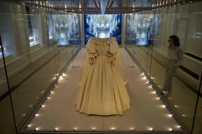 """A staff member poses for photographers next to the wedding dress of Britain's Princess Diana during a media preview for the """"Royal Style in the Making"""" exhibition at Kensington Palace in London, Wednesday, June 2, 2021. The exhibition, which opens to visitors on Thursday and runs until January 2, 2022, explores the intimate relationship between fashion designer and royal client. (AP Photo/Matt Dunham)"""