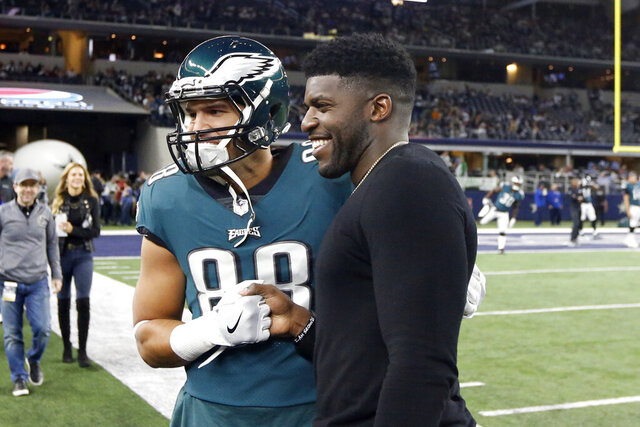"""FILE - In this Nov. 19, 2017, file photo, then-Philadelphia Eagles tight end Trey Burton (88) has a photo taken with former Eagles linebacker Emmanuel Acho prior to an NFL football game against the Dallas Cowboys in Arlington, Texas. Acho has enjoyed a spectacular rise off the field, beginning with his desire to take on racism. Acho celebrated his 30th birthday this week with the official release of his book: """"Uncomfortable Conversations with a Black Man."""" His YouTube series with the same name has already amassed over 65 million views in five months.(AP Photo/Michael Ainsworth, File)"""