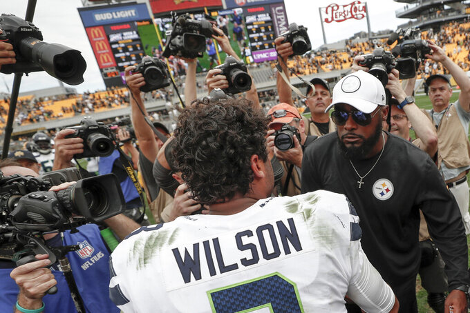 Pittsburgh Steelers head coach Mike Tomlin, right, and Seattle Seahawks quarterback Russell Wilson (3) meet on the field after an NFL football game, Sunday, Sept. 15, 2019, in Pittsburgh. The Seahawks defeated the Steelers 28-26. (AP Photo/Don Wright)