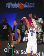 Orlando Magic center Nikola Vucevic (9) shoots over Boston Celtics center Daniel Theis during the first half of an NBA basketball game Sunday, Aug. 9, 2020, in Lake Buena Vista, Fla. (Kim Klement/Pool Photo via AP)