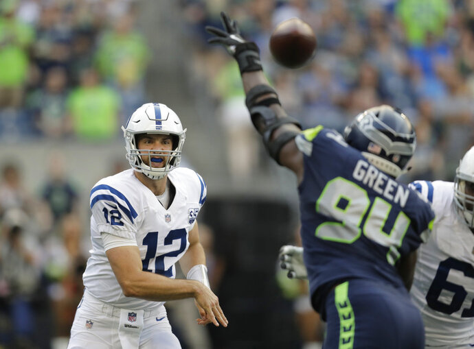 Indianapolis Colts quarterback Andrew Luck (12) passes through the defense of Seattle Seahawks defensive end Rasheem Green during the first half of an NFL football preseason game, Thursday, Aug. 9, 2018, in Seattle. (AP Photo/Stephen Brashear)