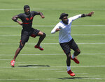FILE - In this Aug. 4, 2020, file photo, Atlanta Falcons wide receivers Calvin Ridley, left, and Julio Jones work on a drill during a team strength and conditioning NFL football workout in Flowery Branch, Ga. It would be easy to overlook Calvin Ridley, being a receiver who plays on the same team as Julio Jones. Ridley, though, has other ideas. Heading into his third year with the Atlanta Falcons, he's planning on a breakout season and making sure everybody knows his name, too. (Curtis Compton/Atlanta Journal-Constitution via AP, File)