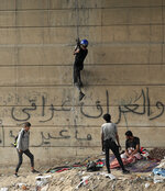 """An anti-government protester climbs the Joumhouriya Bridge that leads to the Green Zone government area, during ongoing protests in Baghdad, Iraq, Sunday, Nov. 3, 2019. Arabic reads, """"Iraq is Iraqi."""" (AP Photo/Hadi Mizban)"""