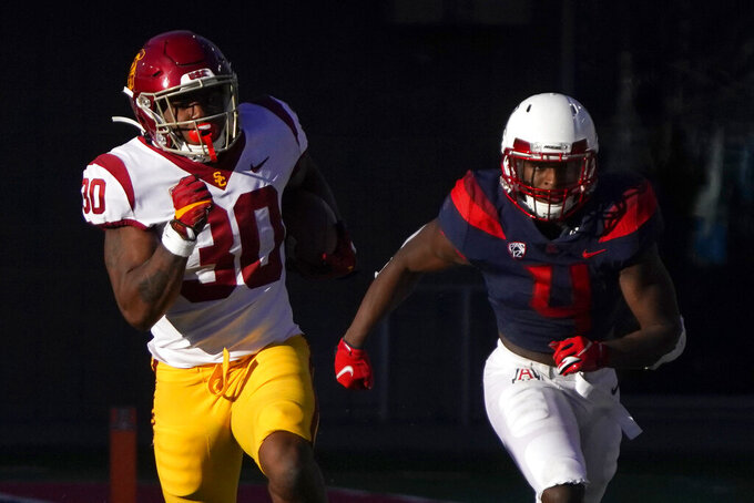 Southern California running back Markese Stepp (30) breaks away from Arizona defensive back Christian Roland-Wallace (4) in the second half during an NCAA college football game, Saturday, Nov. 14, 2020, in Tucson, Ariz. (AP Photo/Rick Scuteri)
