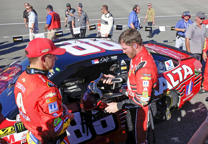 FILE - In this Nov. 19, 2017, file photo, Dale Earnhardt Jr., front right, prepares to climb into his race car before a NASCAR Cup Series auto race at Homestead-Miami Speedway in Homestead, Fla. Dale Earnhardt Jr. is returning to the track Saturday, June 13, 2020, getting behind the wheel for an Xfinity race at Homestead-Miami Speedway -- the place where his Cup Series career ended three years ago. (AP Photo/Gaston De Cardenas, File)