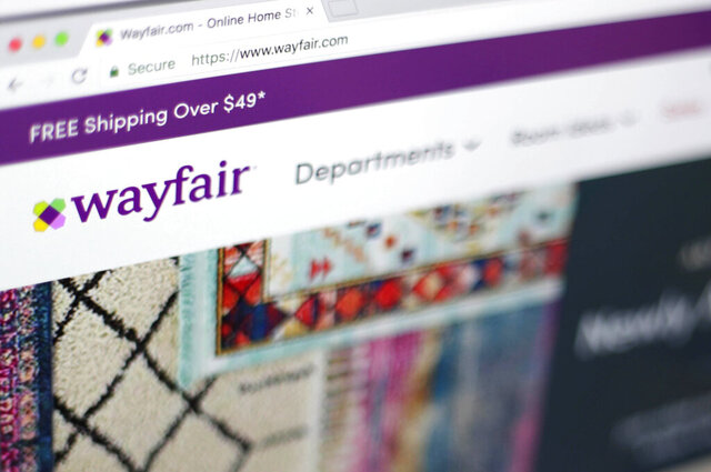 FILE- This April 17, 2018, file photo shows the Wayfair website on a computer in New York. Online furniture seller Wayfair said that it is cutting about 550 jobs, or 3% of its total workforce. Most of the layoffs are at its Boston headquarters and a European office in Berlin. The company has about 17,000 employees worldwide. (AP Photo/Jenny Kane, File)