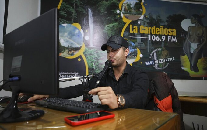 Radio jockey Cristian Sanchez makes a COVID-19 public safety announcement on the local radio station in Campohermoso, Colombia, Thursday, March 18, 2021. According to the town mayor,  the key to Campohermoso being able to stay COVID free is a continuous barrage of public service announcements on the radio and public announcement systems teaching people how to stay safe during the pandemic. (AP Photo/Fernando Vergara)
