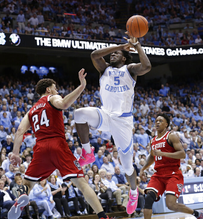 North Carolina's Nassir Little, center, loses the ball while driving to the basket against North Carolina State's Devon Daniels, left, and C.J. Bryce, right, during the first half of an NCAA college basketball game in Chapel Hill, N.C., Tuesday, Feb. 5, 2019. (AP Photo/Gerry Broome)