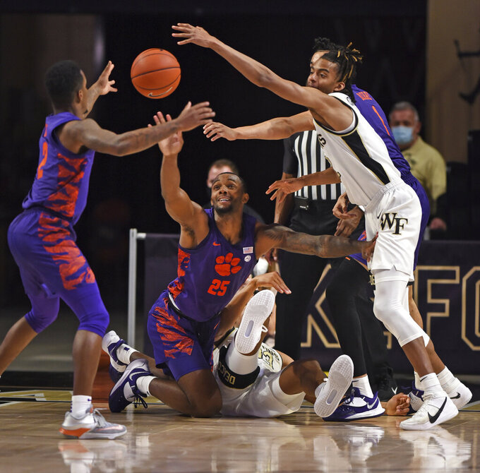 Clemson's Al-Amir Dawes, left, and Aamir Simms compete for a rebound with Wake Forest's Ody Oguama and Jalen Johnson, right, duirng an NCAA college basketball game Wednesday, Feb. 24, 2021, in Winston-Salem, N.C. (Walt Unks/The Winston-Salem Journal via AP, Pool)