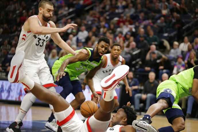 Toronto Raptors guard Kyle Lowry loses the ball as he falls while teammate Marc Gasol (33) and Minnesota Timberwolves forward Andrew Wiggins (22) look on in the second quarter of an NBA basketball game Saturday, Jan. 18, 2020, in Minneapolis. (AP Photo/Andy Clayton-King)