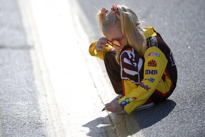 Four-year-old Clover Grant, of Jacksonville, Fla., writes her name on the track before the NASCAR Daytona 500 auto race at Daytona International Speedway, Monday, Feb. 17, 2020, in Daytona Beach, Fla. (AP Photo/Phelan M. Ebenhack)