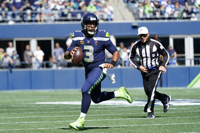 Seattle Seahawks quarterback Russell Wilson scrambles against the Tennessee Titans during the first half of an NFL football game, Sunday, Sept. 19, 2021, in Seattle. (AP Photo/Elaine Thompson)