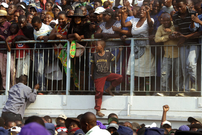 Zimbabweans look on at happening at the Rufaro Stadium in Harare, Thursday, Sept. 12, 2019 where former President Robert Mugabe lies in state for a public viewing. Mugabe, the founder leader, made his final journey back to the country Wednesday amid continuing controversy over where he will be buried. (AP Photo/Themba Hadebe)