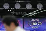 A currency trader works near screens showing the foreign exchange rate between U.S. dollar and South Korean won at the foreign exchange dealing room in Seoul, South Korea, Friday, Oct. 18, 2019. Share prices retreated in Asia after China reported Friday that its economy grew at an annual rate of 6.0% in the latest quarter. (AP Photo/Lee Jin-man)