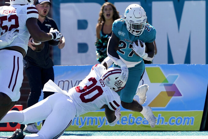 """Coastal Carolina running back CJ Beasley (27) is tackled by Massachusetts' Da""""Shan Ross (30) during the second half of an NCAA college football game on Saturday, Sept. 25, 2021, in Conway, S.C. (AP Photo/Chris Carlson)"""