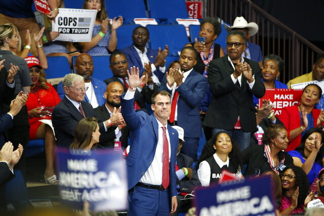 FILE - In this June 20, 2020, file photo, Oklahoma Gov. Kevin Stitt is recognized as President Donald Trump speaks during a campaign rally at the BOK Center, in Tulsa, Okla. Charlie Hannema, spokesperson for Stitt, said Thursday, Aug. 6, 2020, that Stitt, the first governor in the nation to test positive for the coronavirus, was infected when he hugged two friends from Tulsa, on July 10, in Oklahoma City and not connected to the Trump rally. (AP Photo/Sue Ogrocki, File)