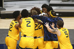West Virginia players celebrate after defeating Texas Tech in an NCAA college basketball game Monday, Jan. 25, 2021, in Morgantown, W.Va. (AP Photo/Kathleen Batten)