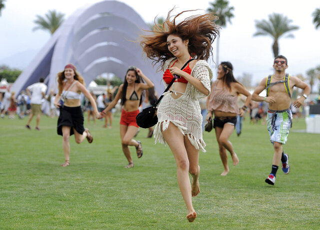 FILE - This April 13, 2012 file photo shows festivalgoers running toward the main stage at the 2012 Coachella Valley Music and Arts Festival in Indio, Calif. The Coachella music festival in Southern California has been postponed amid virus concerns. The festival is organized by concert promoter Goldenvoice, which released a statement Tuesday saying it will be rescheduled for two weekends in October. For most people, the new coronavirus causes only mild or moderate symptoms, such as fever and cough. For some, especially older adults and people with existing health problems, it can cause more severe illness, including pneumonia. The vast majority of people recover from the new virus. According to the World Health Organization, people with mild illness recover in about two weeks, while those with more severe illness may take three to six weeks to recover. (AP Photo/Chris Pizzello, File)