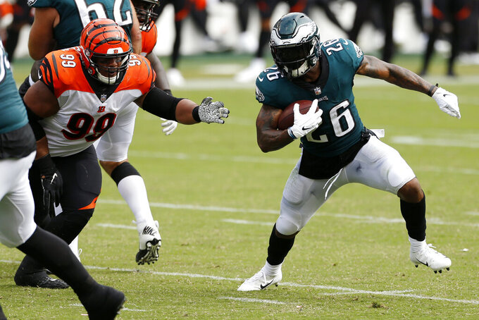 Philadelphia Eagles' Miles Sanders (26) tries to rush past Cincinnati Bengals' Christian Covington (99) during the second half of an NFL football game, Sunday, Sept. 27, 2020, in Philadelphia. (AP Photo/Laurence Kesterson)