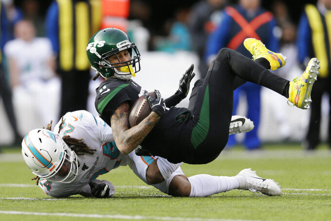 Miami Dolphins cornerback Ryan Lewis (24) tackles New York Jets wide receiver Robby Anderson (11) during the first half of an NFL football game, Sunday, Dec. 8, 2019, in East Rutherford, N.J. (AP Photo/Adam Hunger)